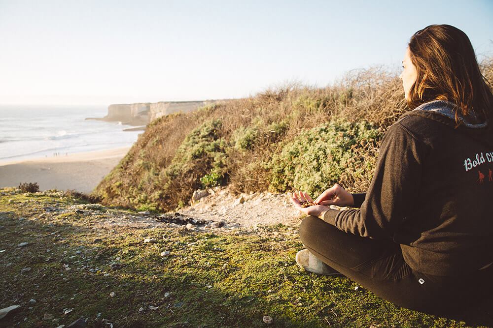 A girl sits overlooking the ocean snacking on organic trail mix