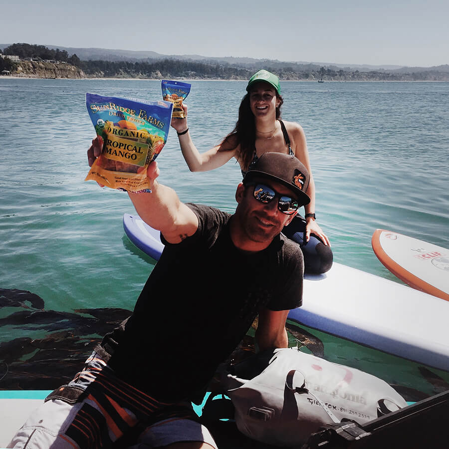 Big wave surfer Tyler Fox holds out his SunRidge Farms tropical mango after paddle boarding