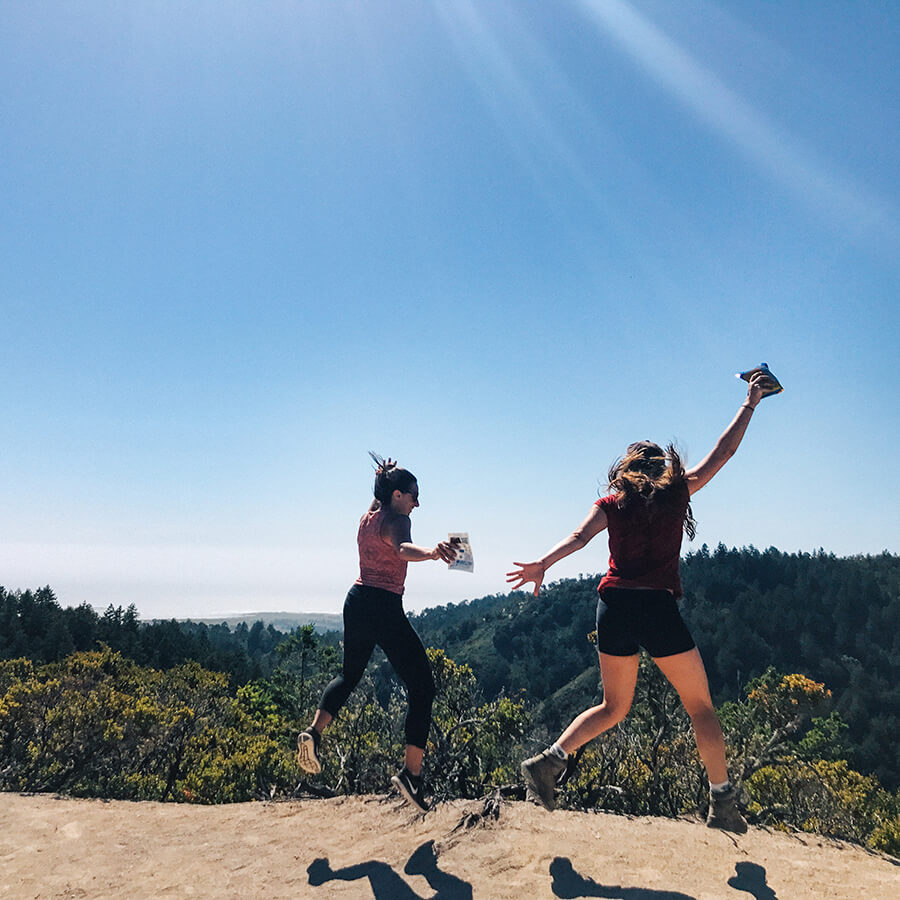 girls jump with excitement with their hiking snacks from SunRidge Farms in Big Basin California